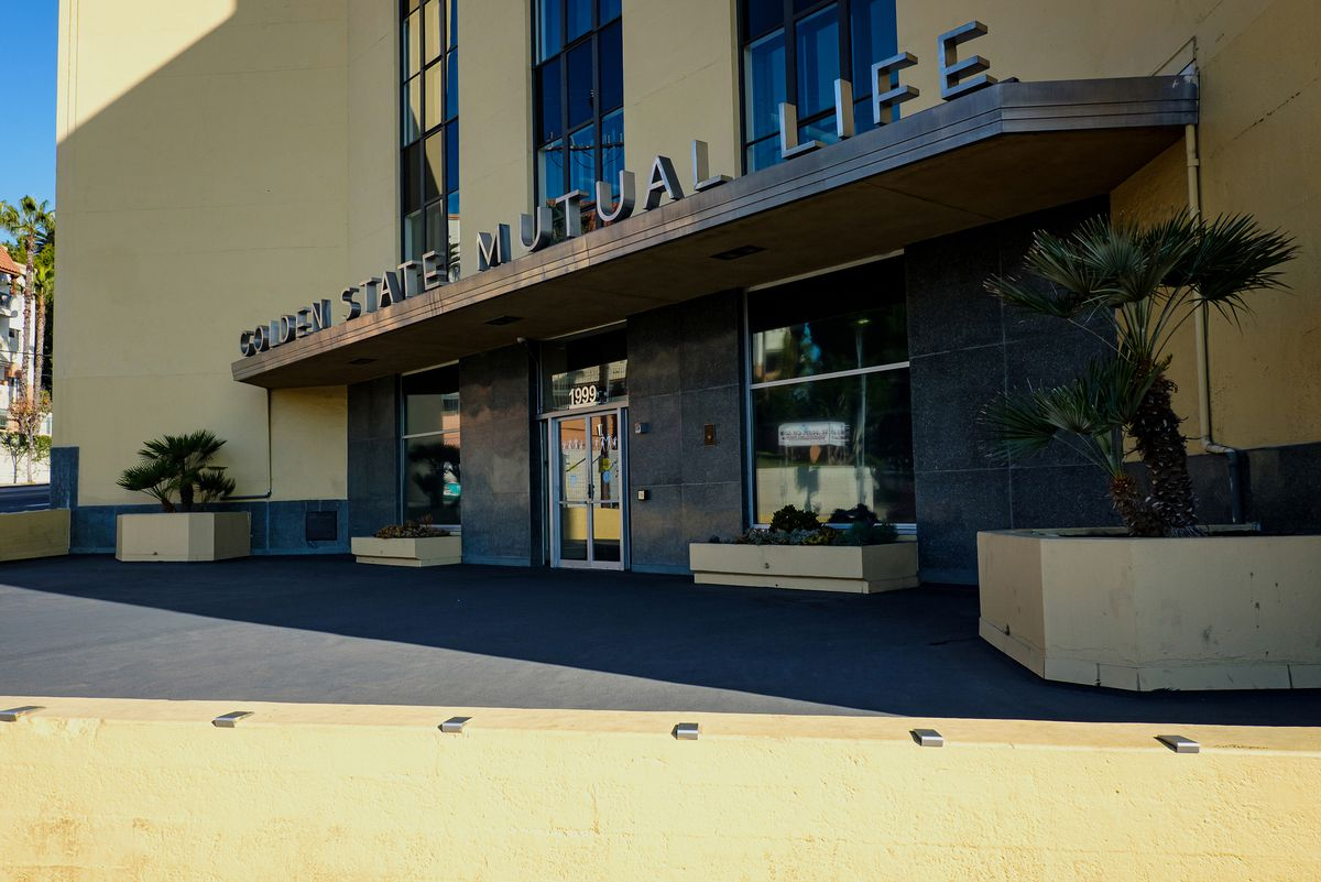 """The entrance to a yellow, mid-rise building. There is a single entry door and on a ledge over the door, metal letters spell out """"Golden State Mutual Life."""""""