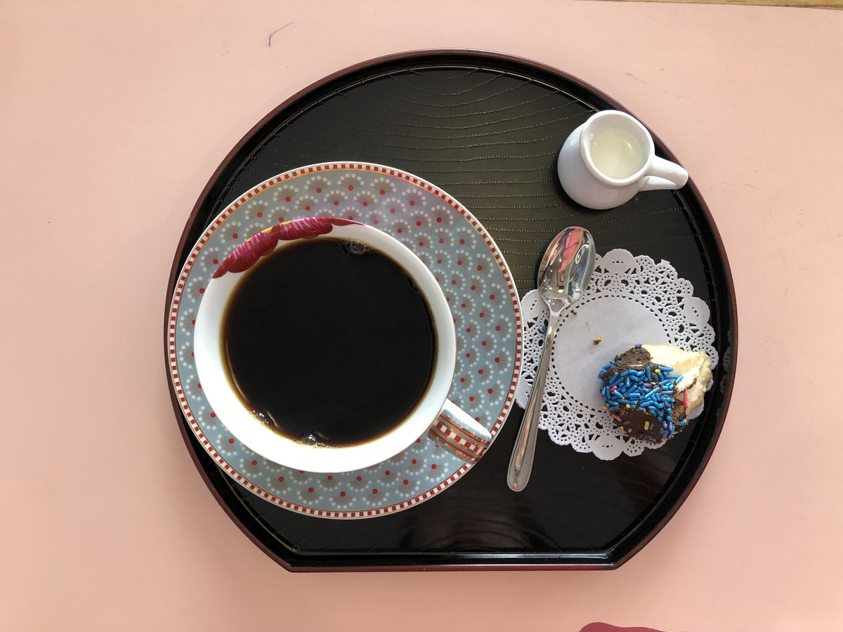 a cup of black tea on a decorative plate with a doily and cookie with sprinkles to the right
