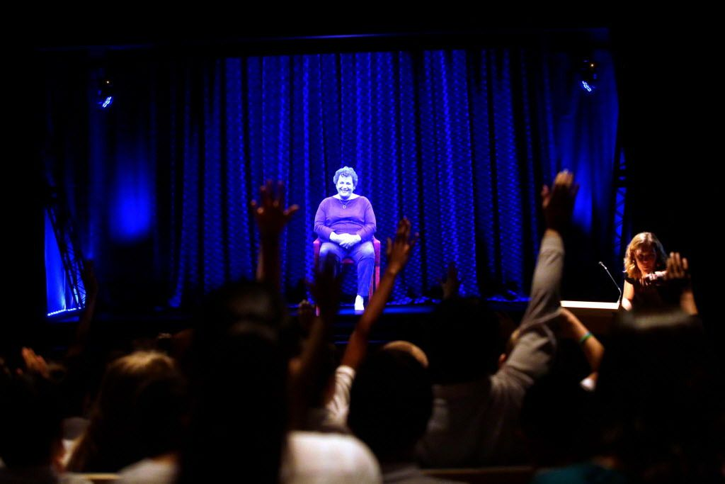 Students raise their hand as they direct questions to Holocaust survivor Adina Sella as she is displayed on a three-dimensional hologram at the Take A Stand Center in the Illinois Holocaust Museum & Education Center on October 26, 2017, in Skokie, Ill