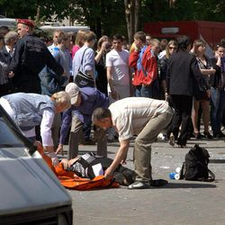 People assist an injured person after an explosion in Dnipropetrovsk, Ukraine, Friday, April 27, 2012. Officials say four blasts within minutes have rocked the center of the eastern Ukrainian city of Dnipropetrovsk, injuring dozens of people, including schoolchildren, in what prosecutors believed was a terrorist attack.