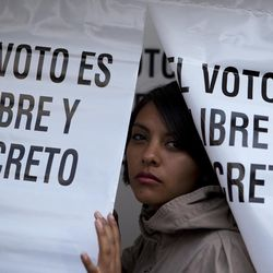"""A woman emerges from a privacy booth, reading in Spanish """"The vote is free and secret,"""" after marking her ballot for governor at a polling station in Chimalhuacan, Mexico state, Sunday, June 4, 2017. Voters in Mexico's most populous state on Sunday could hand the ruling party a much-needed boost ahead of next year's presidential elections or a potentially devastating blow by throwing off its uninterrupted 88-year local rule."""