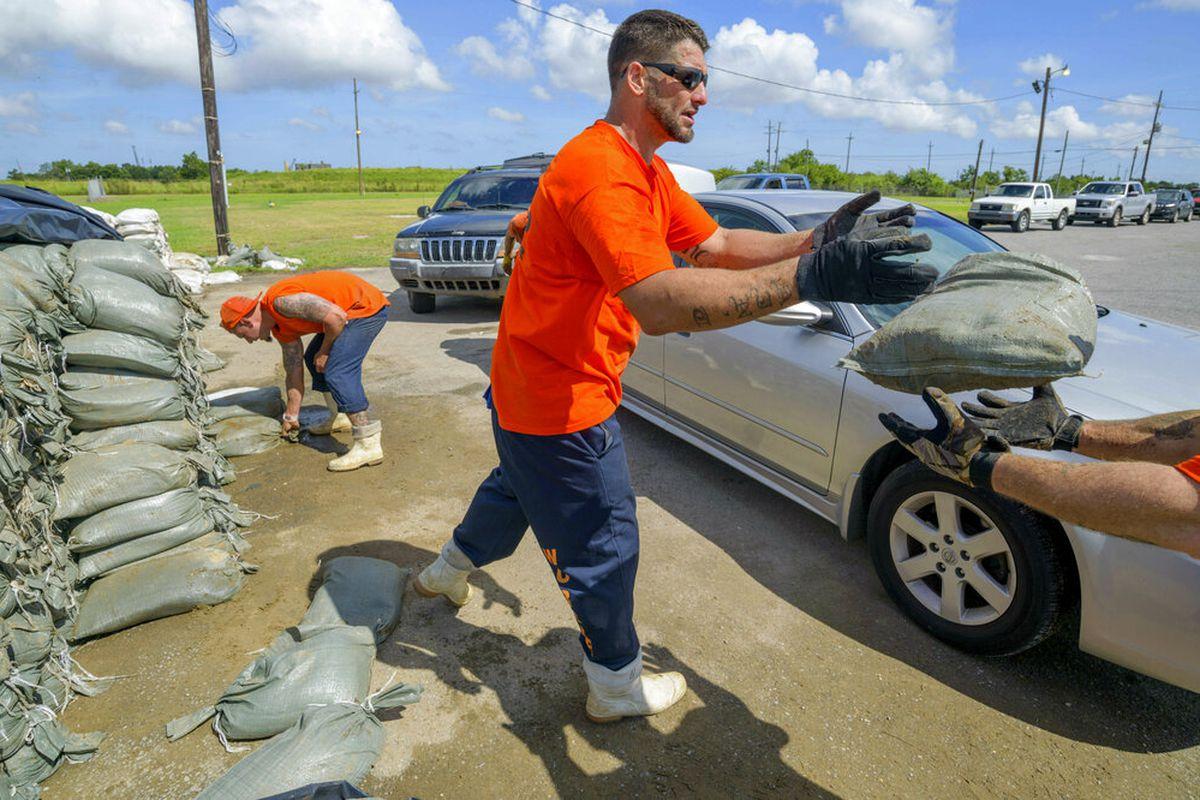 St. Bernard Parish Sheriff's Office inmate worker moves sandbags for person in Chalmette, La.