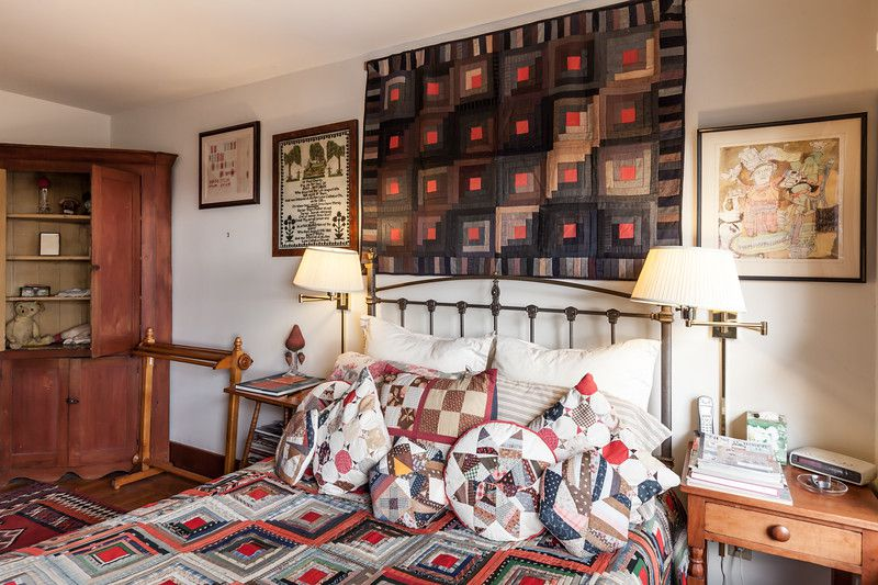 A bed with patterned bed linens and pillows. Above the bed are multiple works of art and a quilt. There is a dresser.