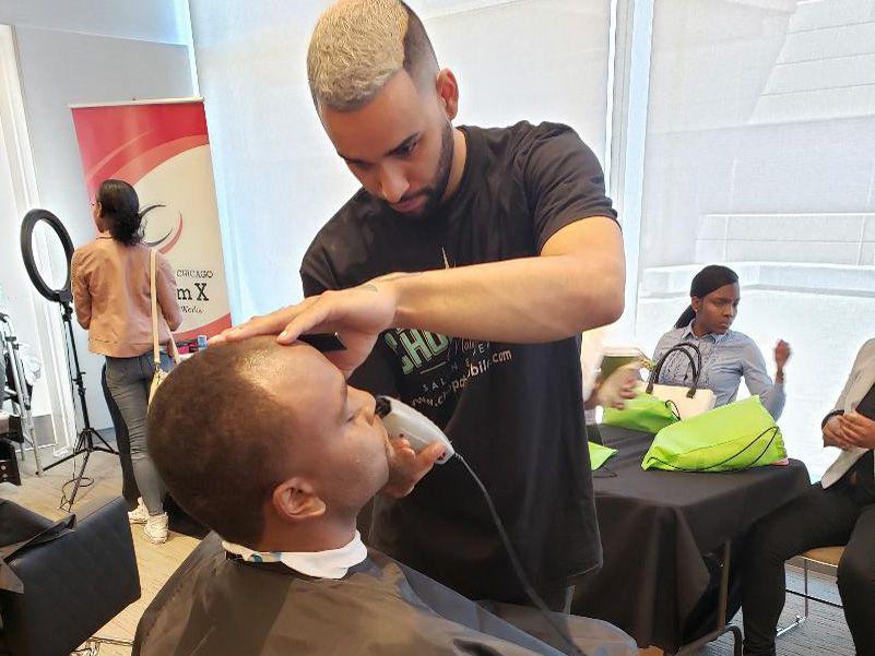 A jobseeker gets a free haircut at LeadersUp's job fair.