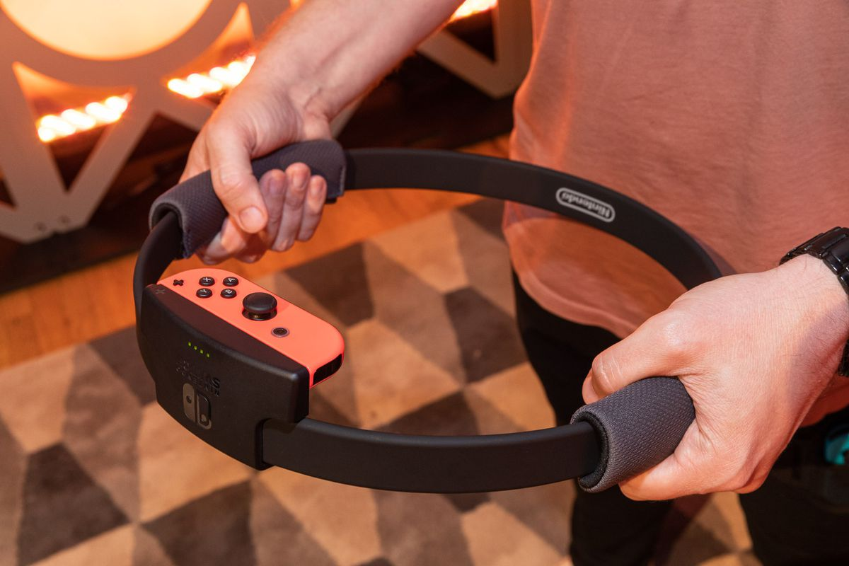 the Nintendo Switch Ring-Con Controller being held by a person wearing an orange shirt