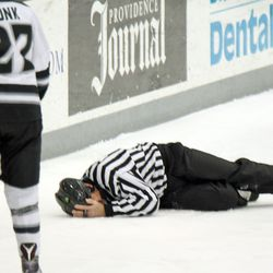 Linesman Chris Millea lies on the ice after hitting his head when he collided with a UConn player.