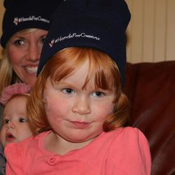 Ann Earl, 35, and her daughter, Alice, 5 months, and Ellie, 4, sport #HandsForCosmas hats. The hats are being sold by youths in Mapleton to raise money for a Opedmoth Cosmas, a 23-year-old Ugandan, to fly to Utah and be fitted with prosthetic hands. Cosmas lost his hands when they were caught in a grinding machine on Jan 12.