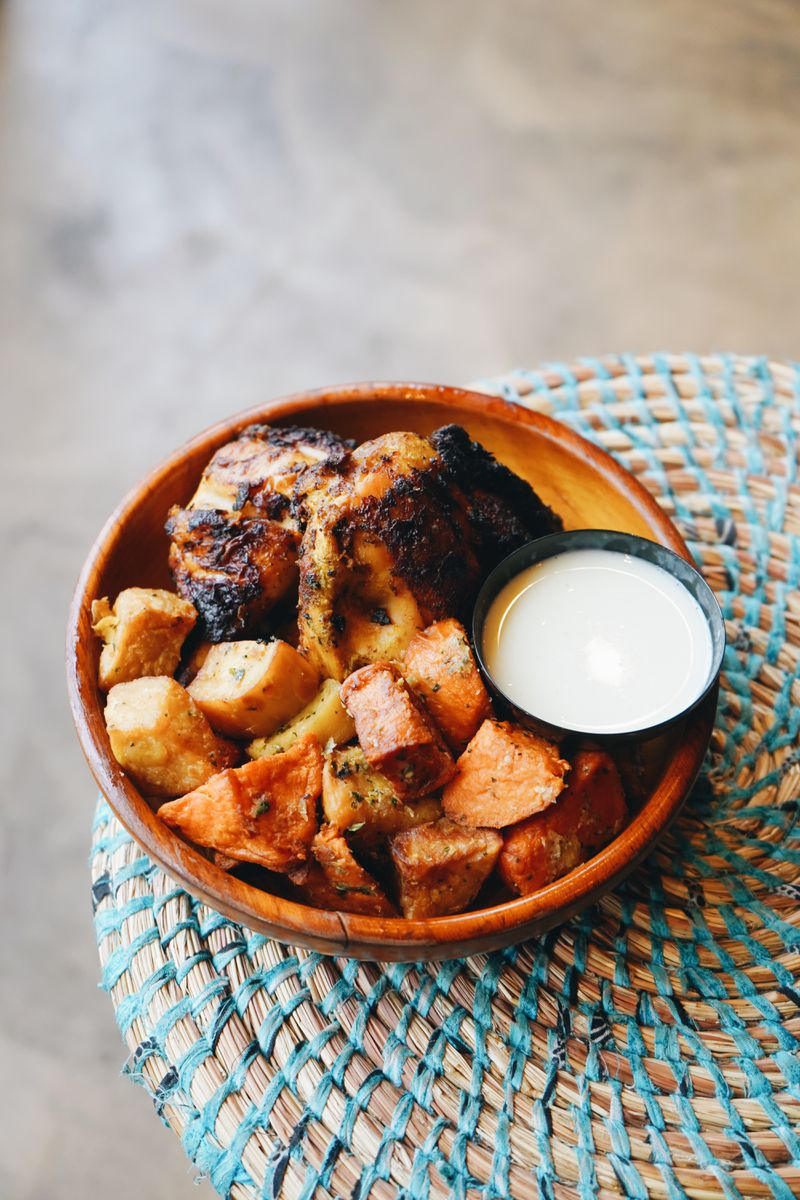 A wooden bowl containing an order of braised chicken with sweet potatoes and a small container of white sauce.