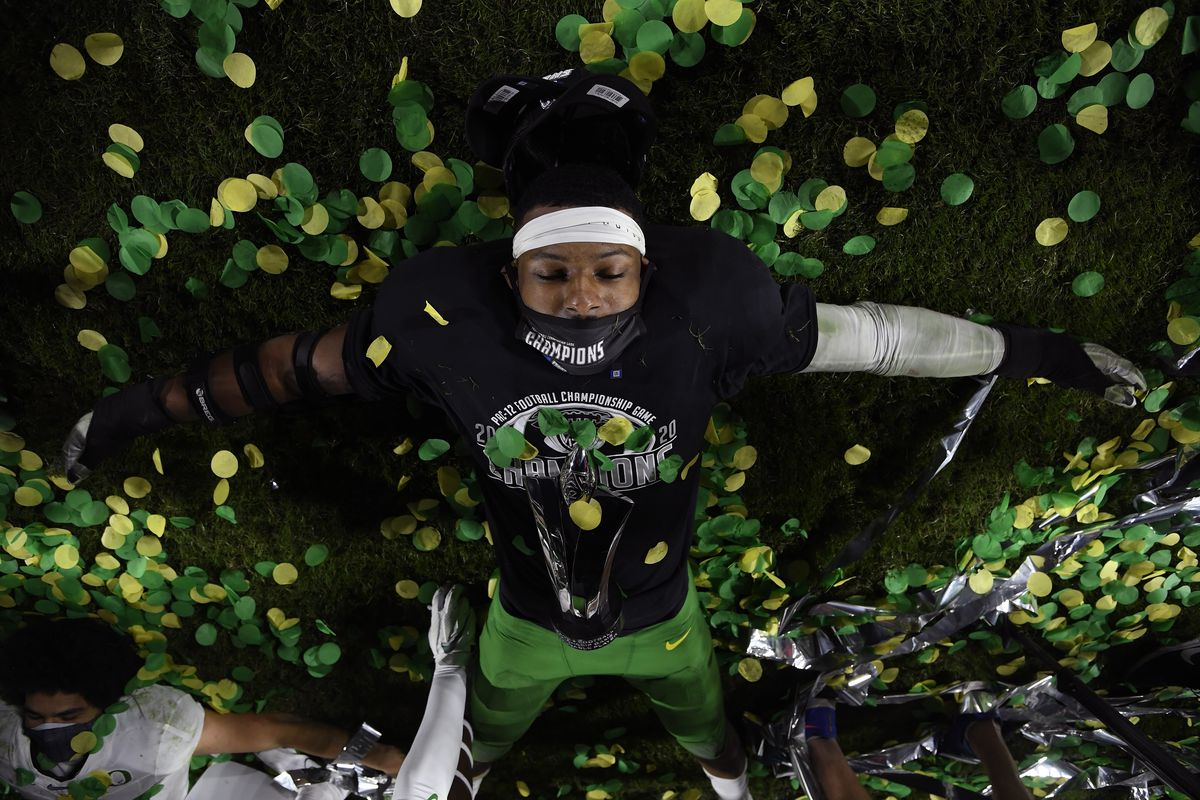 Most valuable player of the game, Kayvon Thibodeaux #5 of the Oregon Ducks, celebrates a 31-24 win over the USC Trojans by making a snow angel on the field with confetti during the PAC 12 2020 Football Championship at United Airlines Field at the Coliseum on December 18, 2020 in Los Angeles, California