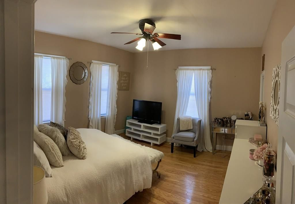 A bedroom with a bed and a ceiling fan, and a TV facing the bed.