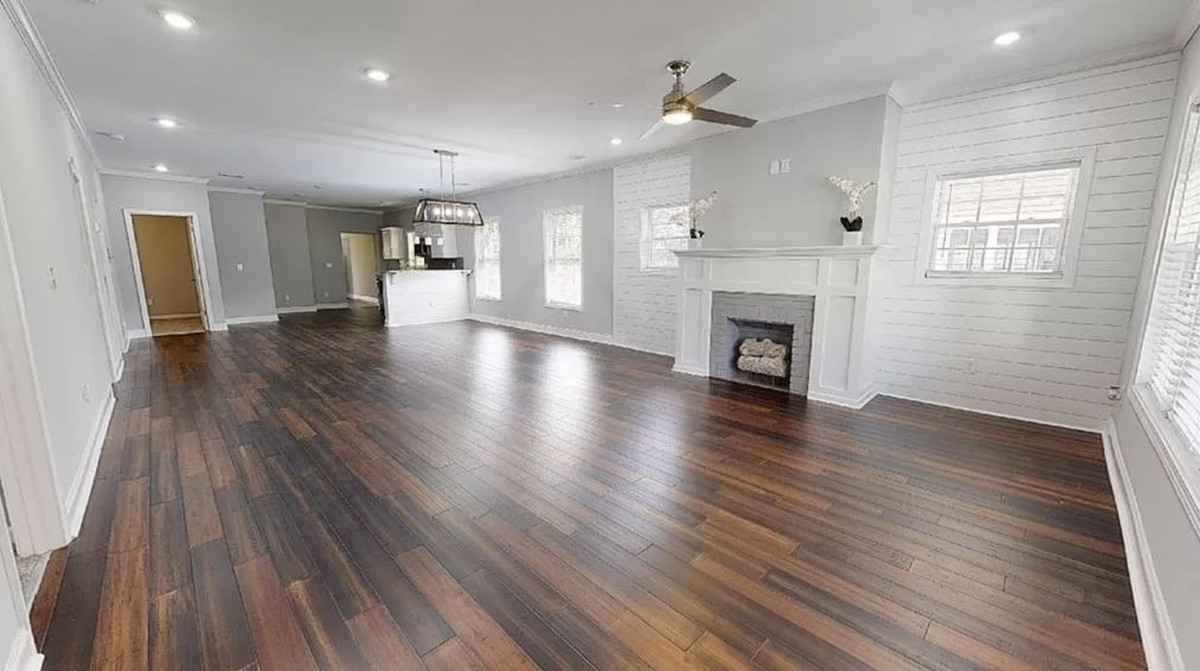 Large open room with fireplace in front and kitchen in the back.