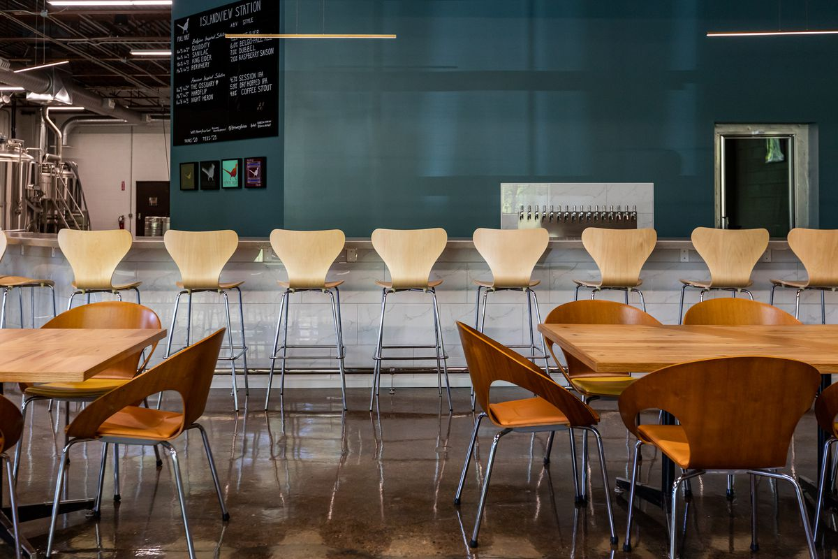 Bar chairs line the concrete bar in front of a silver beer tap system.