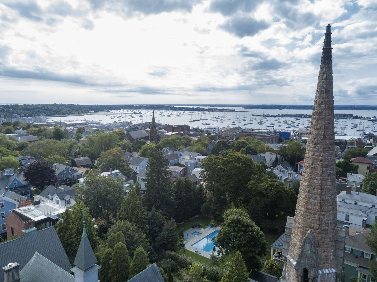 A rooftop view shows the skyline of Newport, Rhode Island, with church steeples, trees, homes, a pool, and a harbor with boats in the distance.