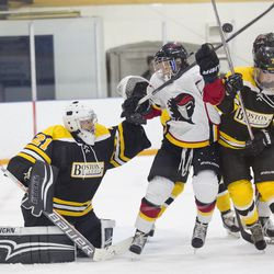 Boston Blades goaltender Jetta Rackleff looks for the puck above two players' heads.