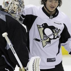 Pittsburgh Penguins goalie Marc-Andre Fleury, left, talks with teammate Arron Asham during the NHL hockey team's practice in Pittsburgh Tuesday, April 17, 2012. The Penguins face the Philadelphia Flyers in Game 4 of the opening round of a NHL hockey playoffs series in Philadelphia on Wednesday. The Flyers lead the best of seven series 3-0.