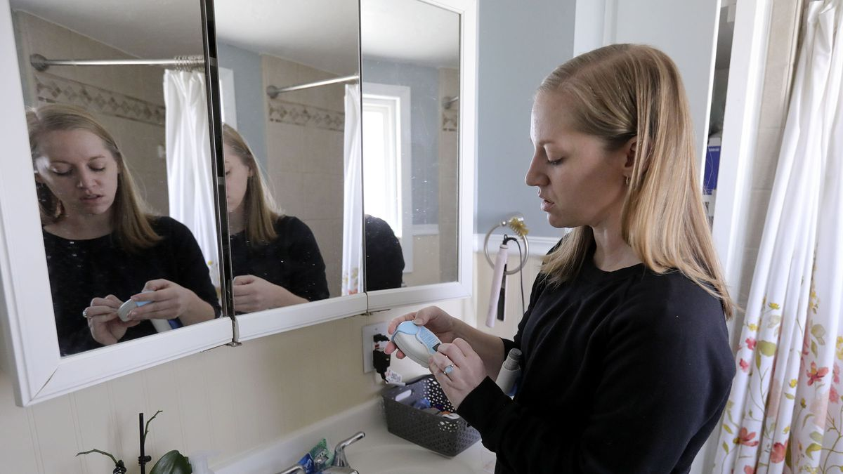 Annie Jarman shows a new inhaler her doctor suggested she try at her home in Murray on Tuesday, Nov. 24, 2020. Jarman tested positive for COVID-19 on July 8, about a week after symptoms started, and still has lingering symptoms.