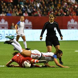 Alex Morgan goes in hard, and goes down hard.