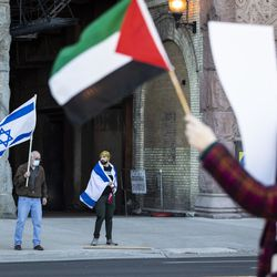Two counter-protesters wave Israel's flag as thousands rally in support of Palestine on Michigan Avenue near Grant Park, Wednesday evening, May 12, 2021.