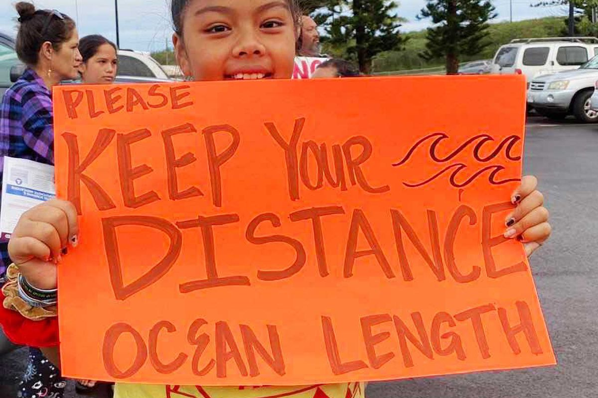 "A young girl holds a sign that reads, ""Please keep your distance ocean length."""