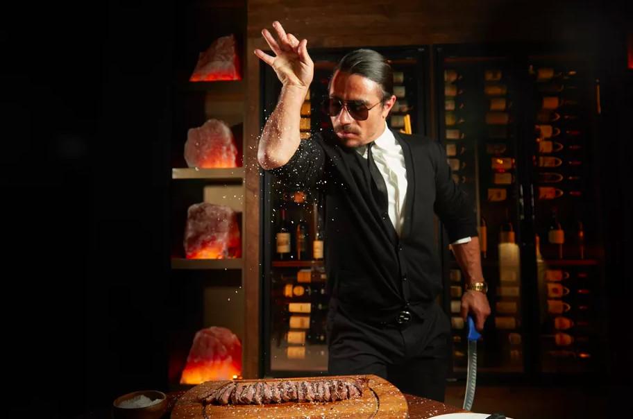 Salt Bae doing his signature salt-dashing move over a sliced steak