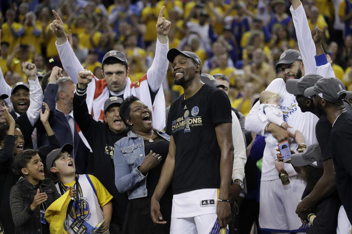 Golden State Warriors forward Kevin Durant, center, celebrates with his mother Wanda Durant as he is named the NBA Finals Most Valuable Player after Game 5 of basketball's NBA Finals between the Warriors and the Cleveland Cavaliers in Oakland, Calif., Mon