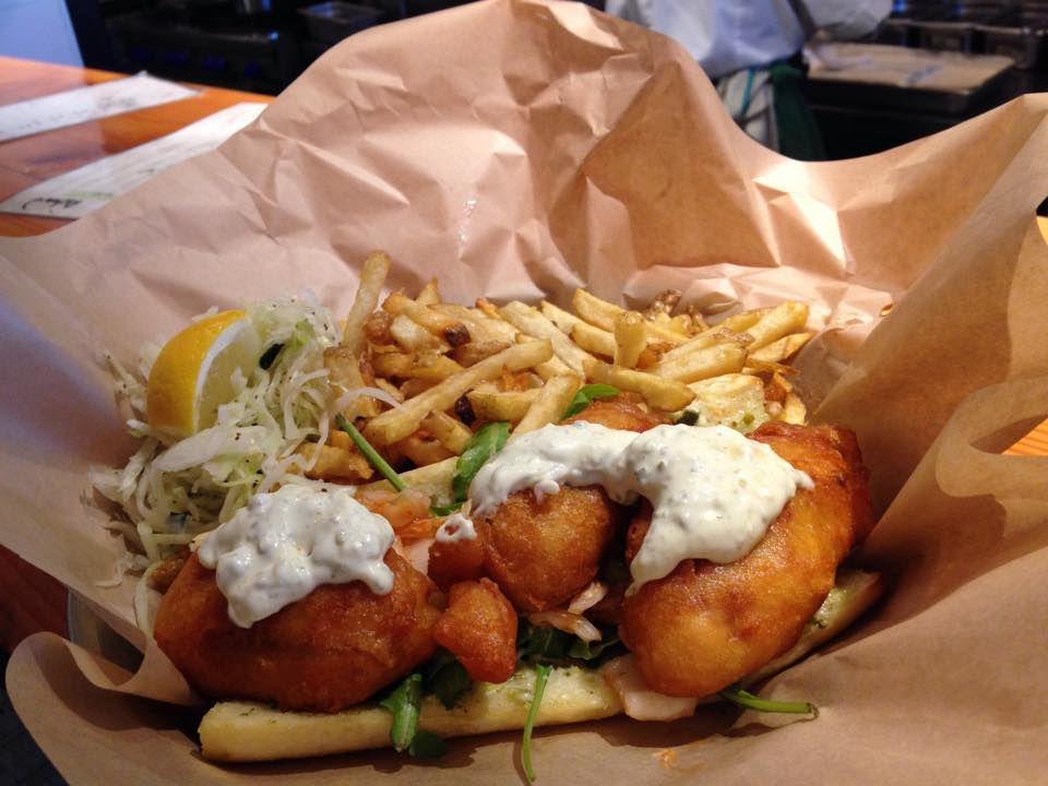 Fried fish topped with tartar sauce and herbs, fries, and a lemon wedge in wax paper