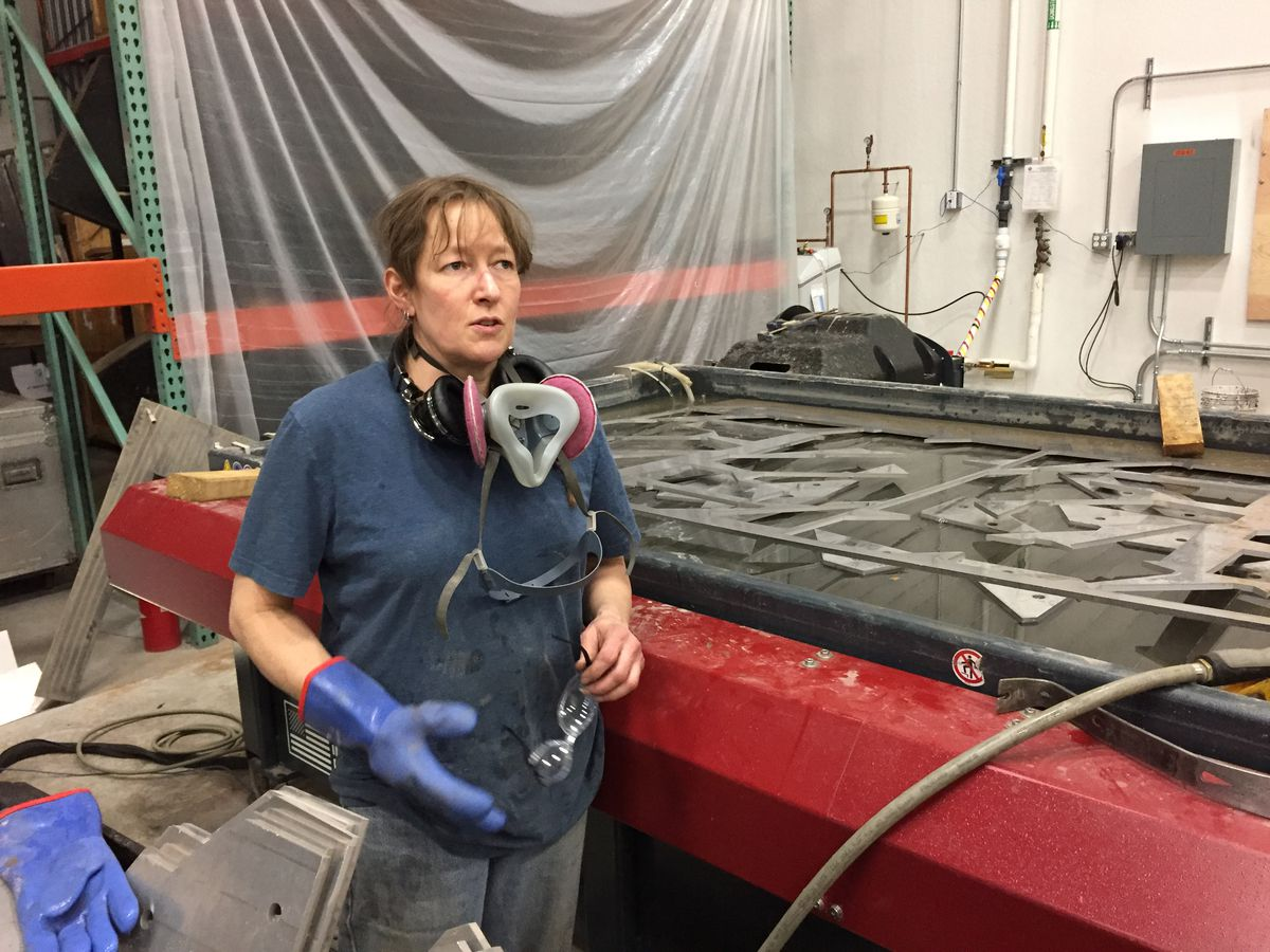 Beth Smith, head of the metal department at Chicago Scenic Studios, uses a water jet to cut through half-inch thick aluminum plate to make supports for a truss arch that will decorate Northwestern's April 21 Starry Night gala. | Neil Steinberg/Sun-Times
