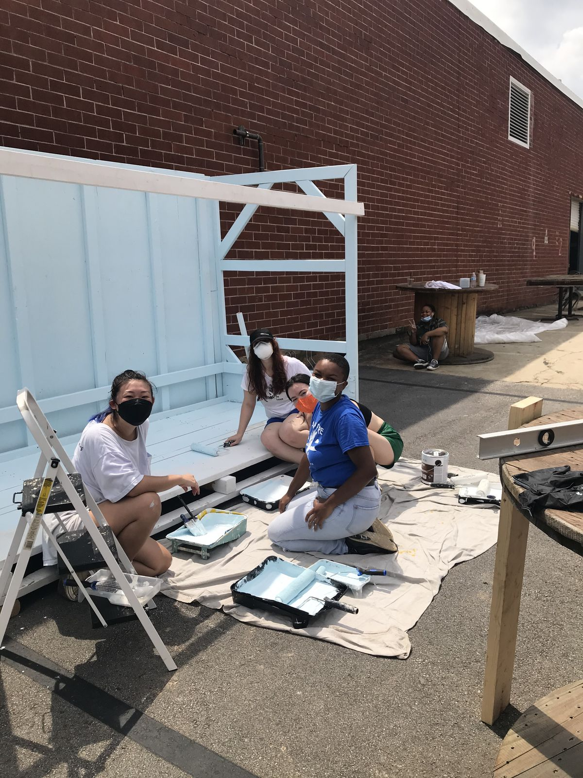 Three masked volunteers sitting on the ground painting the food pantry shelter white at Best End Brewing