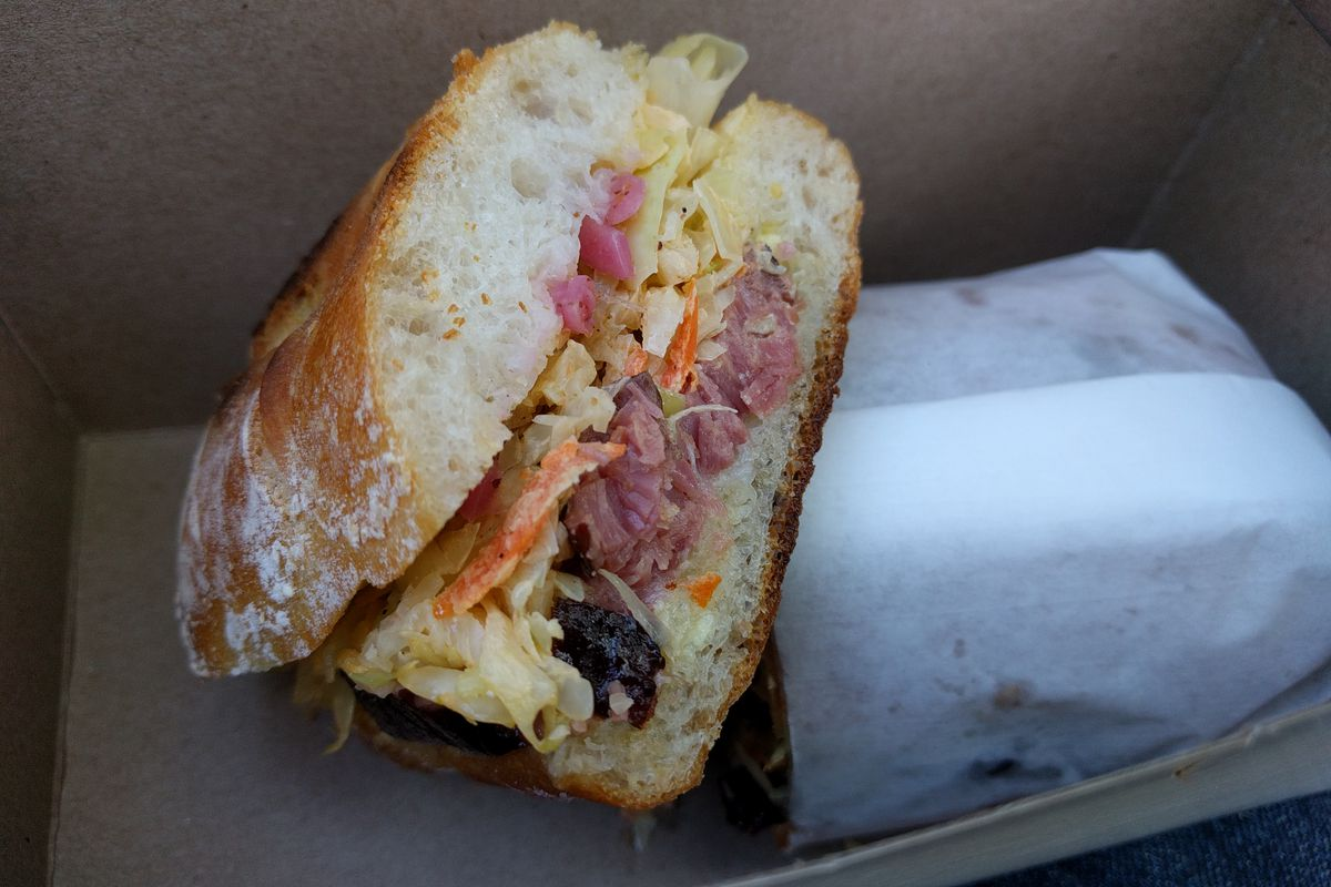 A sandwich on a demi baguette is cut to reveal boneless smoked ribs and cole slaw.