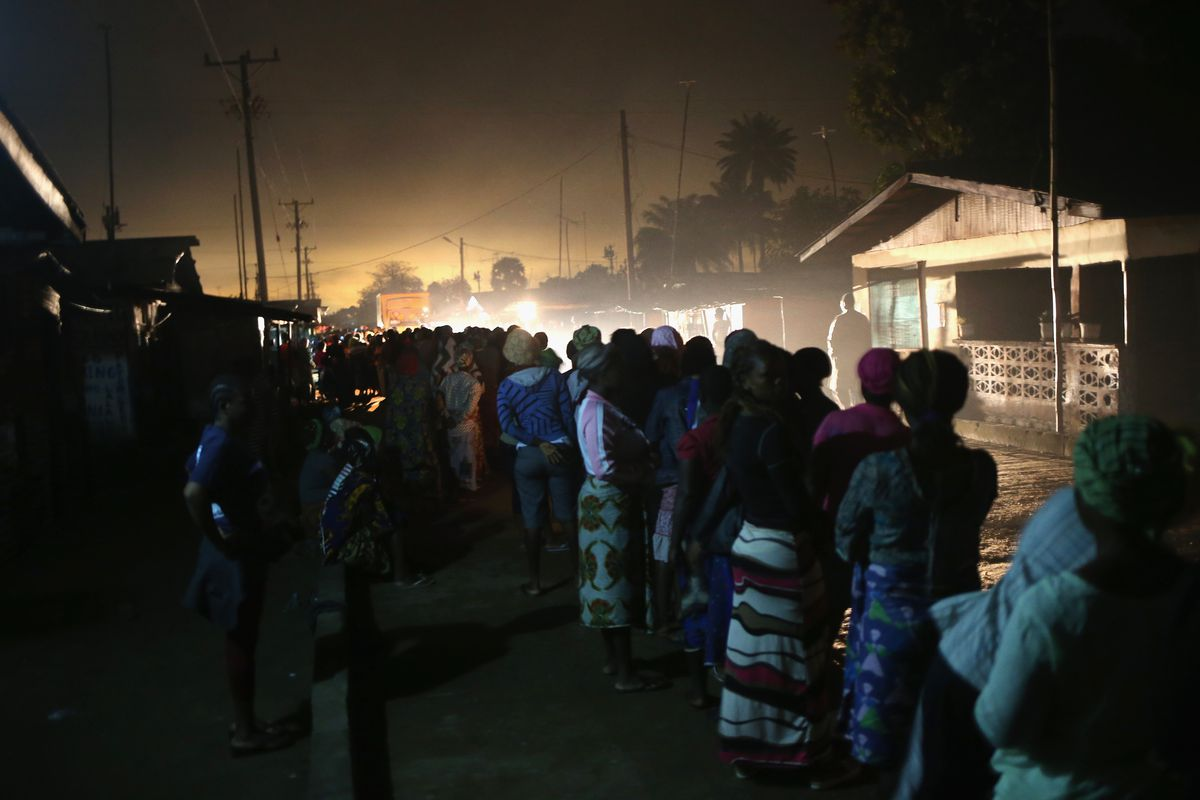 Residents of an Ebola affected township wait in line before dawn to receive family and home disinfection kits in New Kru Town, Liberia.