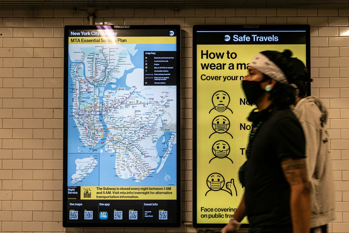 """Riders walk past a """"how to wear a mask"""" MTA sign at the Times Square station on June 10, 2020."""