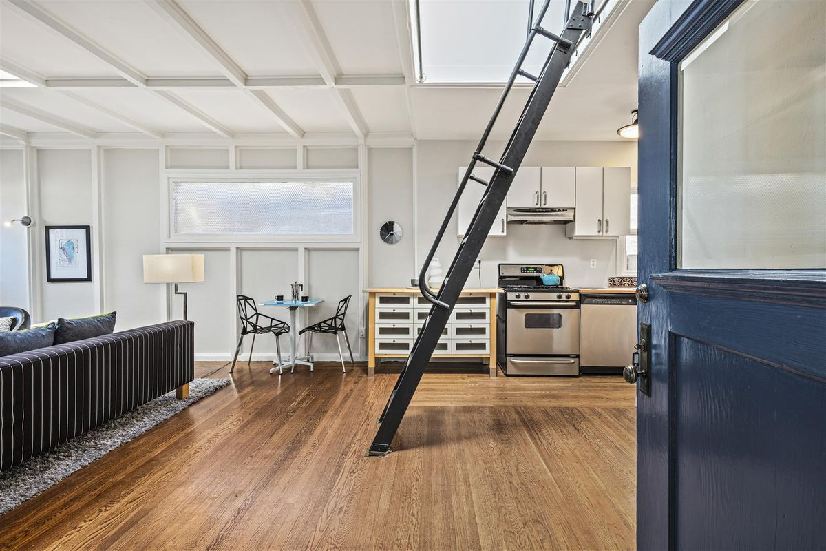 A blue door opens to a living room with hardwood floors, a black metal ladder leading to a loft, and a kitchen space.