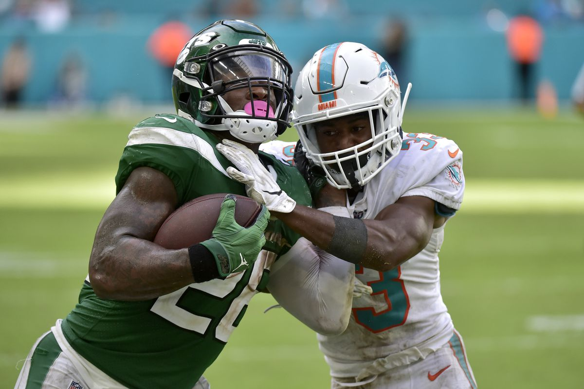 Le'Veon Bell of the New York Jets is tackled by Jomal Wiltz of the Miami Dolphins during the fourth quarter of the game at Hard Rock Stadium on November 3, 2019 in Miami, Florida.