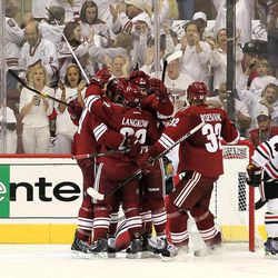 Phoenix Coyotes' Michal Rozsival (32), of the Czech Republic, Daymond Langkow (22) and Keith Yandle celebrate a goal by Taylor Pyatt, second from left, between Chicago Blackhawks' Jamal Mayers (22) and Niklas Hjalmarsson (4), of Sweden, during the second period in Game 1 of an NHL hockey Stanley Cup first-round playoff series, Thursday, April 12, 2012, in Glendale, Ariz.