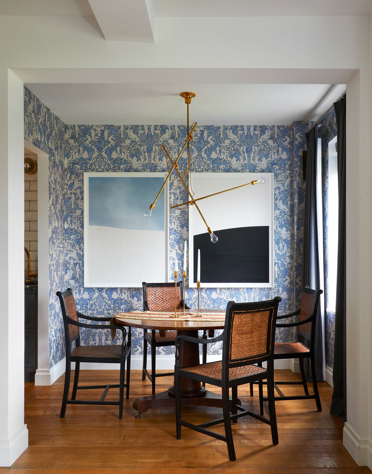 The modern blue-and-white wallpaper and brass chandelier are juxtaposed with an antique dining table and chairs from the 1840s.