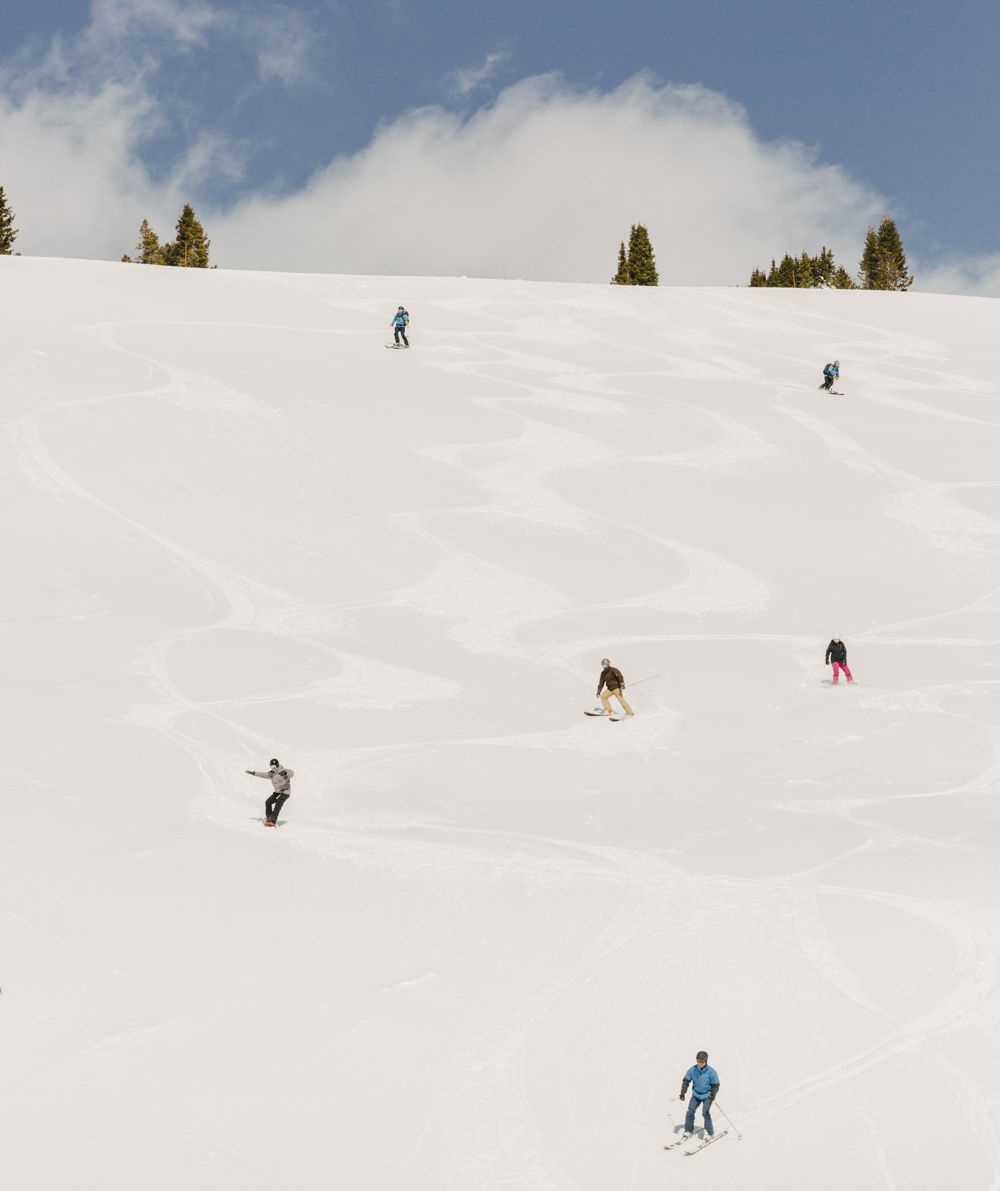 6 skiers colorfully dressed, coming down a mountain.