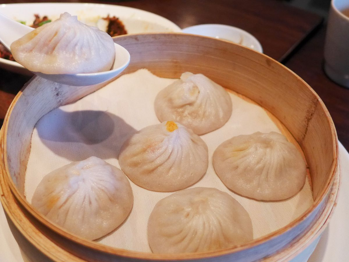 Six pork and crab xiao long bao in a bamboo steamer, with one lifted up on a spoon