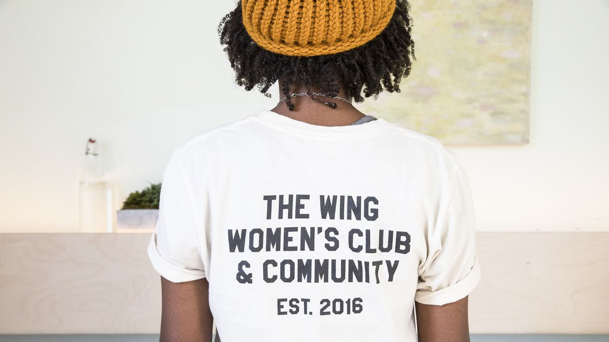 """A woman in a t-shirt that reads """"The Wing women's club & community, established 2016."""""""