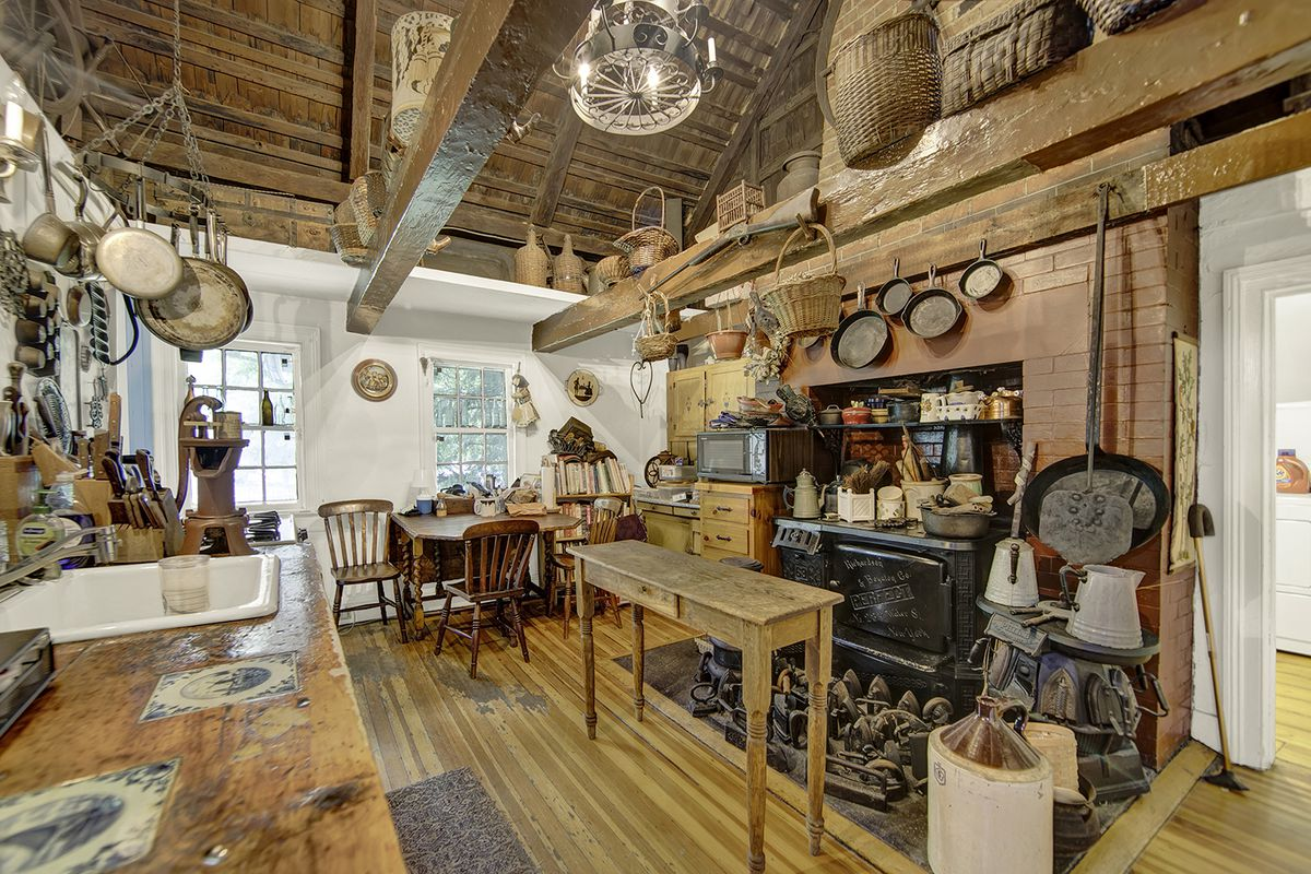 A country kitchen with vaulted ceilings, exposed brick, and pots and pans hanging from wood beams.