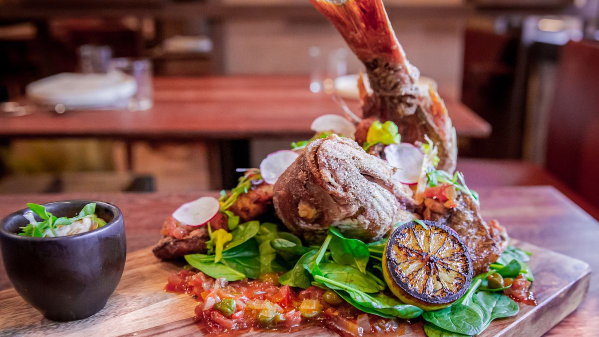 A large crispy whole fish with its tail lifted up served over Mexican salad with sauce.