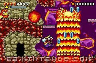 Wario Land 4 Game Boy game screenshot, Wario is jumping over lava. The art style is pixelated.
