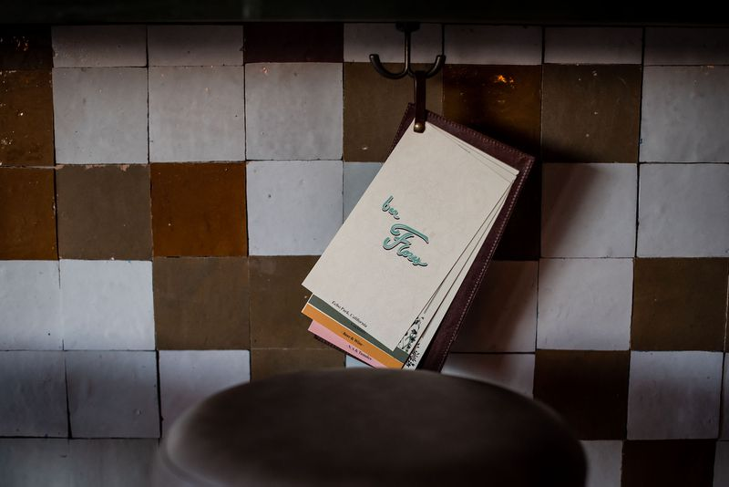 Menu hanging from under the bar counter with white and brown tiles.