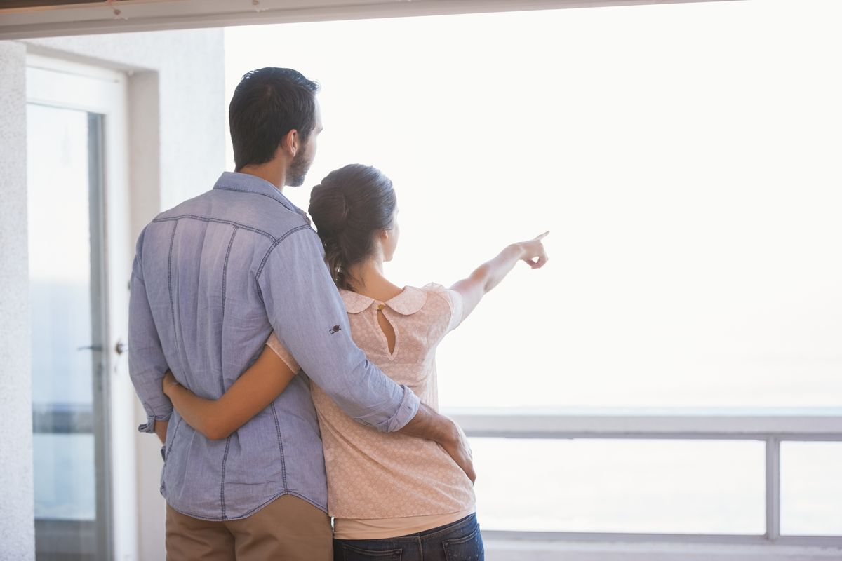 Couple in roomy apartment, pointing out the window