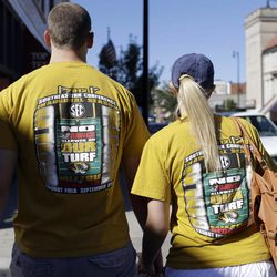 John Kowalski, left, and his girlfriend Laura Gomski wear shirts referring to an NCAA college football game between Georgia and Missouri as they walk down a street before the start of the game Saturday, Sept. 8, 2012, in Columbia, Mo. The football game will be the first for Missouri against a Southeastern Conference opponent since joining the conference.