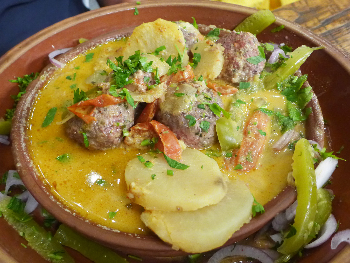 Meatballs, sliced-thin potatoes, and peppers bathe in an oily yellow broth in a brown bowl.