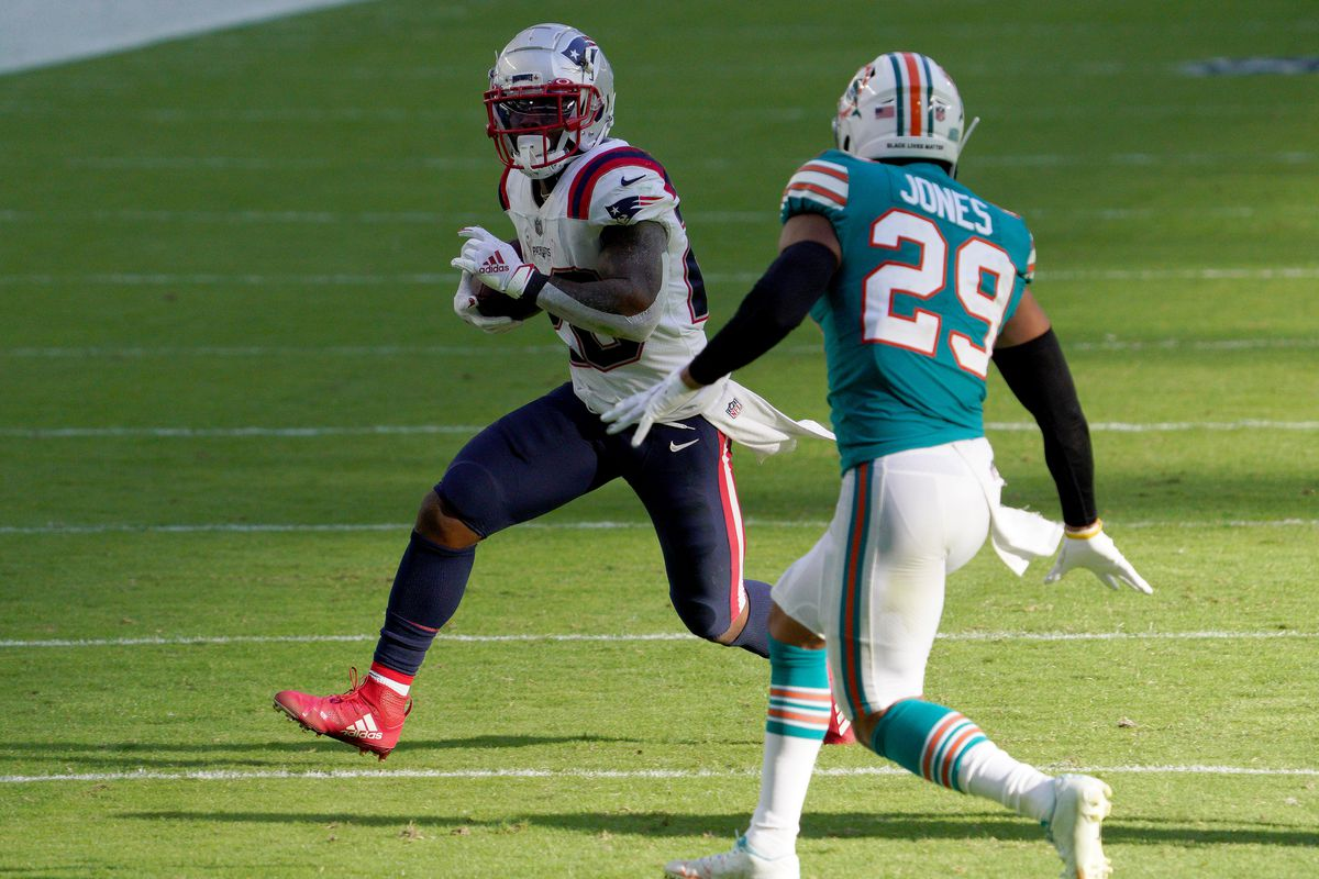 Sony Michel #26 of the New England Patriots carries the ball against Brandon Jones #29 of the Miami Dolphins during the fourth quarter in the game at Hard Rock Stadium on December 20, 2020 in Miami Gardens, Florida.