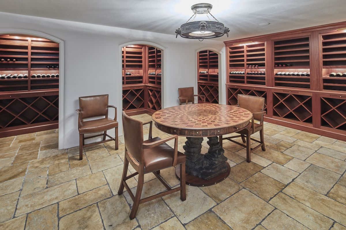 A spacious wine storage room has stone floors, a small round table, and wine shelves throughout.