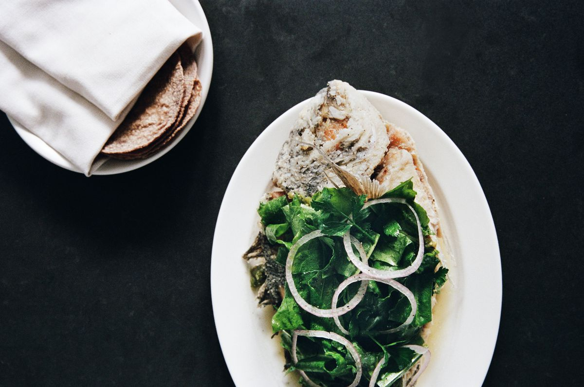 A fried fish covered in herbs with a side of tortillas.