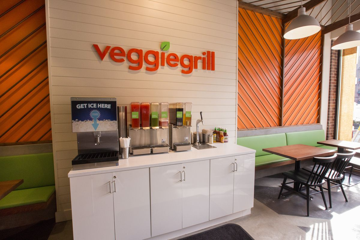 """A wall with the words """"Veggie Grill"""" in orange above a condiment stand."""