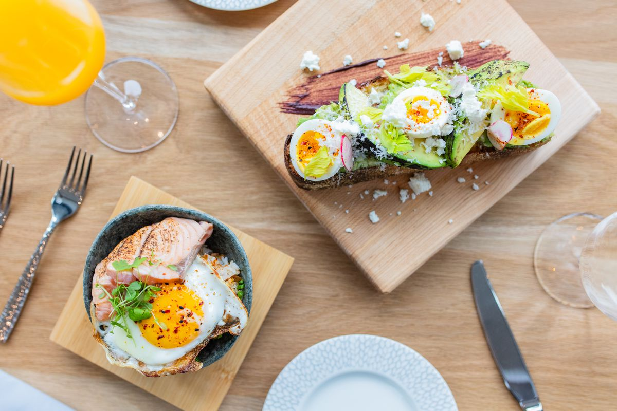 An overhead shot showing avocado toast plated on a wooden board, with an adjacent bowl filled with salmon and a fried egg